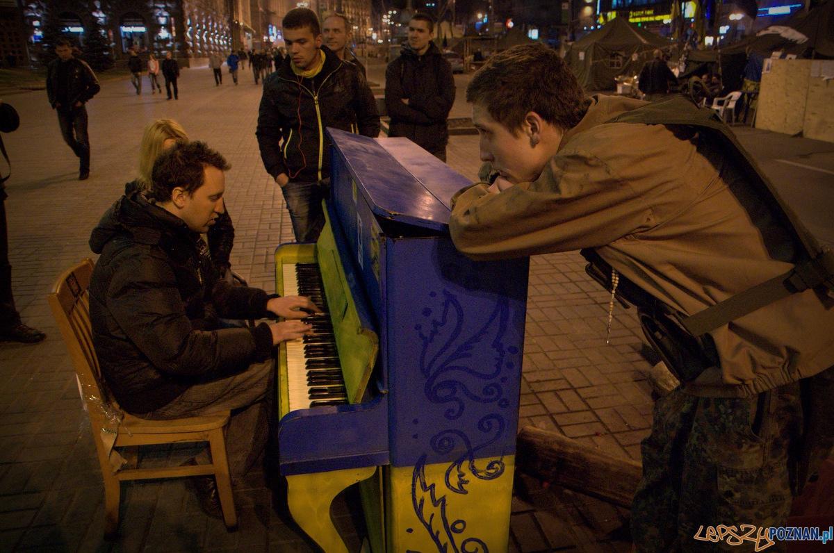 """Przed jednym z budynków obleganych przez rewolucjonistów zostało wystawione pianino pomalowane na barwy ukraińskie i unijne. Każdy może usiąść i zagrać melodię dla przechodniów. Ten chłopak zagrał motyw przewodni z filmu """"Titanic"""". Wymowne!  Foto: lepszyPOZNAN.pl / Mathias Mezler"""